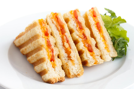 toasted sandwich: Classic tomato and cheese toasted sandwich on white plate.