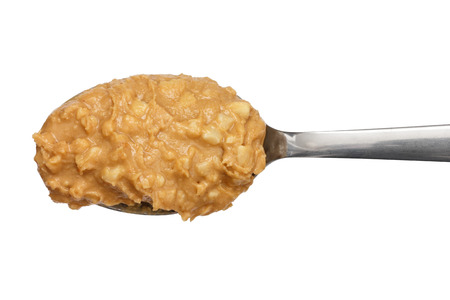Crunchy peanut butter on metal spoon. Stock Photo