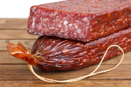 Premium salami, cut on wood grain surface. photo