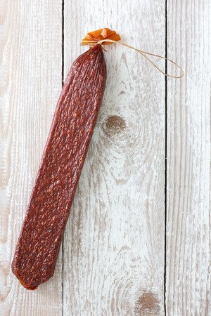 grease paint: Premium stick of salami with string isolated on white painted board. Stock Photo