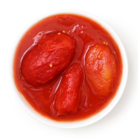 vegetable tin: Whole canned tomatoes in white dish. Isolated above. Stock Photo