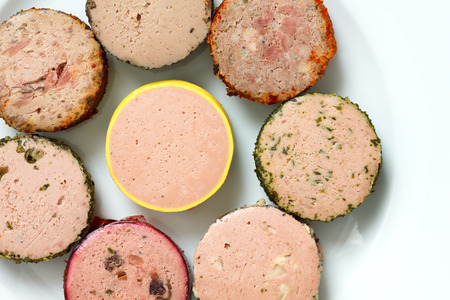 kinds: Many kinds of round pates on plate. From above.