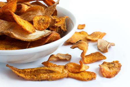 Schüssel mit gebratenen Karotten und Pastinaken Chips. Auf weiß.