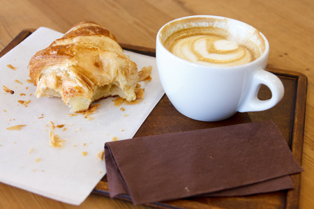 eaten: Half eaten croissant with cappuccino on wood tray and table.