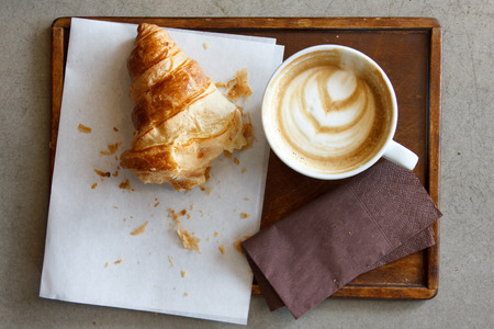 eaten: Half eaten croissant with cappuccino on wood tray from above.