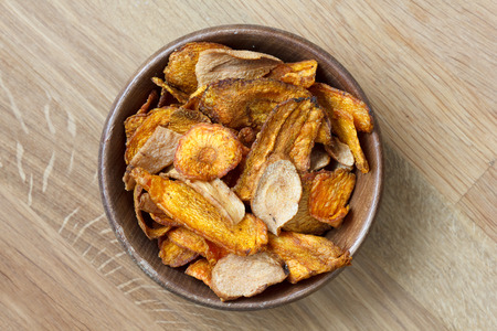 parsnip: Fried carrot and parsnip chips in rustic wood bowl. From above. Stock Photo