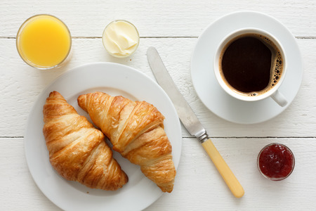 continental: Coffee orange juice and croissant breakfast. From above.