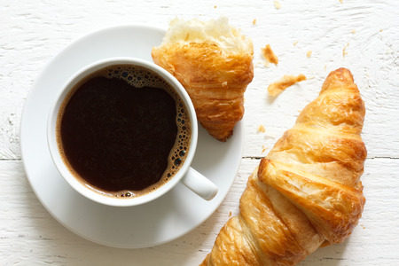 Croissants and coffee on rustic white wood from above.