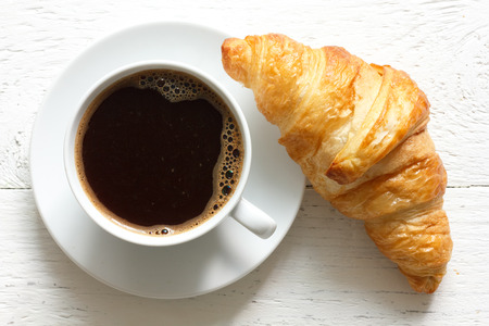 Croissant and coffee on rustic white wood from above.