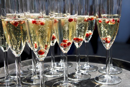 a pomegranate: Sparkling champagne flutes on tray with pomegranate seeds.