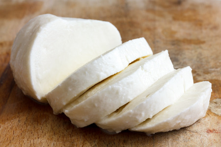 large ball: Single ball of mozzarella cheese sliced and isolated on rustice wood. Stock Photo