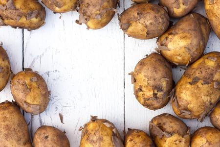 unwashed: Unwashed patate novelle su legno bianco rustico. Spazio per il testo.