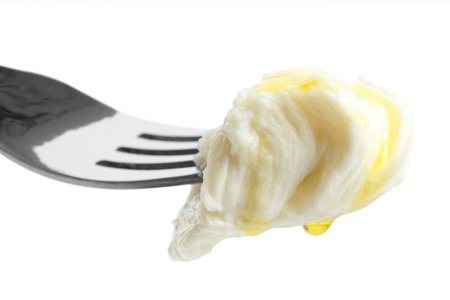 mouthful: Mouthful of torn mozzarella dripping with oil on fork and isolated.