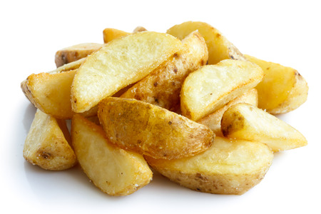 Heap of fried potato wedges isolated on white.
