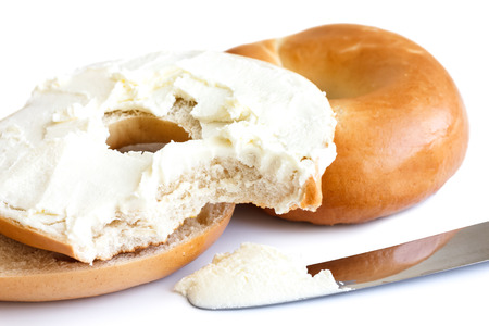 bagel: Plain bagel with knife, spread with cream cheese and bite missing. Stock Photo