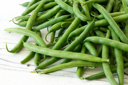 snap bean: Whole French green string beans  on white rustic wood. Stock Photo