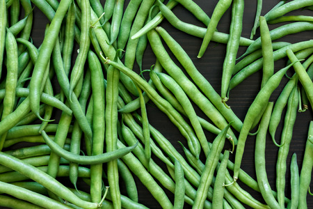 snaps: Whole French green string beans  on black rustic surface. Stock Photo