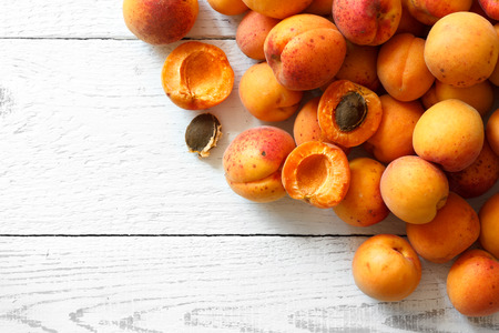 apricot kernels: Whole orange apricots with red blush, from above, space for text. Open apricot with stone. On rustic white wood.