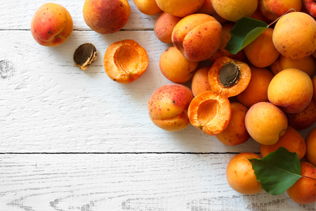 apricot kernel: Whole orange apricots with red blush, from above, space for text. Open apricot with stone and leaves. On rustic white wood. Stock Photo