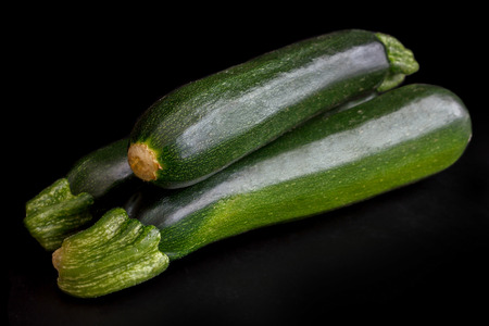 courgettes: Stack of whole courgettes isolated on black. Stock Photo