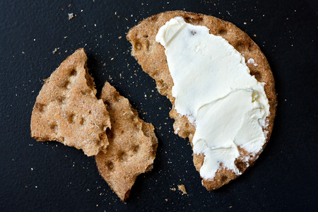 hard cheese: Single broken rye crispbread with cream cheese, from above, isolated on black.