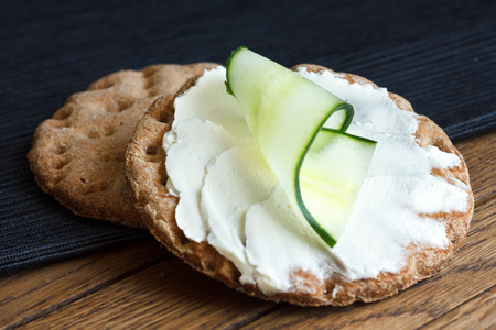 hard cheese: Two round rye crispbreads on wood with black napkin. Top one spread with cream cheese and cucumber slice.