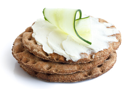 Stack of round rye crispbreads isolated on white. Top one spread with cream cheese and cucumber slice. Stock Photo