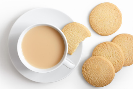 biscuit: White cup of tea and saucer with shortbread biscuits from above.