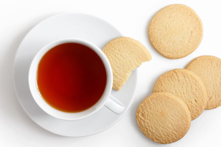 shortbread: White cup of tea and saucer with shortbread biscuits from above.