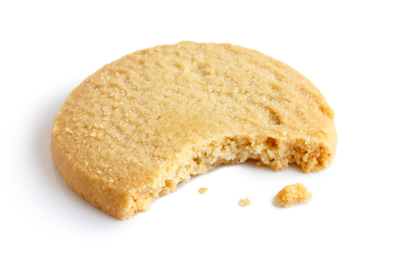 biscuit: Single round shortbread biscuit with crumbs and bite missing. In perspective.
