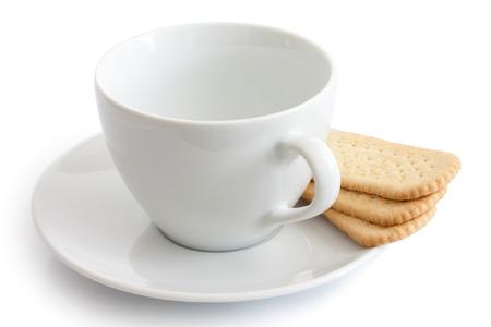 galletas: Vaciar taza de cerámica blanca y un plato con galletas de té dedo. Aislados.