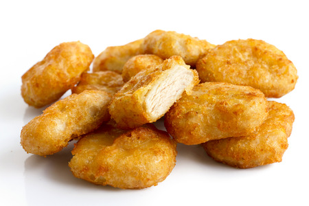 Pile of golden deep-fried battered chicken nuggets isolated on white. One cut with meat showing. Stockfoto