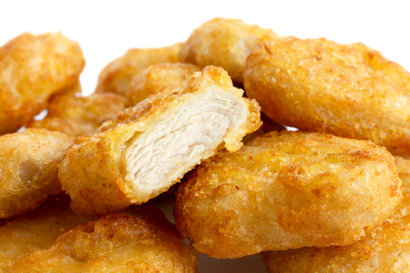 Detail of golden deep-fried battered chicken nuggets with white background. One cut with meat showing.