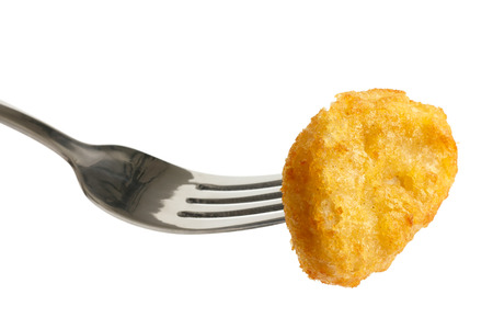 battered: Single golden deep-fried battered chicken nugget on a fork isolated on white. Stock Photo