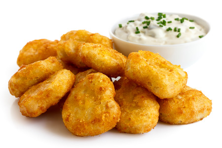 battered: Pile of golden deep-fried battered chicken nuggets with bowl of tartar sauce, isolated on white.