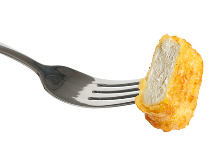 battered: Single golden deep-fried battered chicken nugget on a fork isolated on white. Cut with meat texture showing. Stock Photo