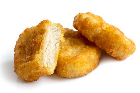 pollo: Tres nuggets de pollo rebozados fritos de oro aislado en blanco en perspectiva. Un corte con la demostraci�n de la carne. Foto de archivo