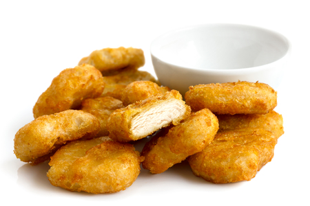 chicken nuggets: Pile of golden deep-fried battered chicken nuggets with empty bowl, isolated on white. Stock Photo