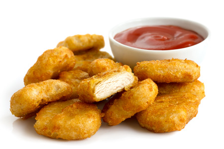 battered: Pile of golden deep-fried battered chicken nuggets with bowl of ketchup, isolated on white. Stock Photo