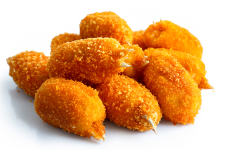 Pile of fried breaded surimi crab claws, in perspective, isolated on white.