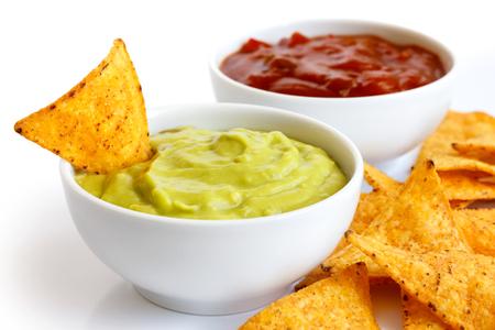 Runde weiße Schüssel Dip Guacamole in Perspektive isoliert. Tortilla-Chips herum und in Dip. Schüssel Tomatensalsa im Hintergrund. Standard-Bild