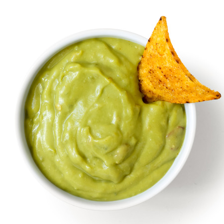 Round white bowl of guacamole dip with tortilla chip, isolated from above.