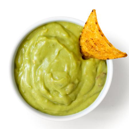 Runde weiße Schale mit Guacamole-Dip mit Tortilla-Chips, isoliert von oben.