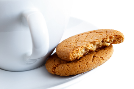 two and a half: Detail of two ginger biscuits, one broken in half, with cup and saucer. White background.