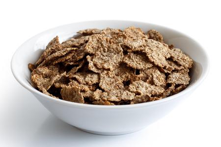 cereales: El salvado de trigo cereal de desayuno con leche en un recipiente aislado en fondo blanco.