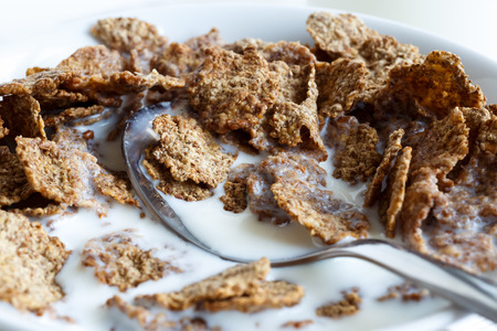eaten: Detail of half eaten wheat bran breakfast cereal with milk and spoon in bowl. Stock Photo