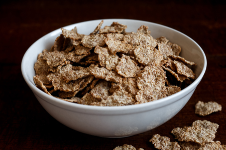 spilt: Wheat bran breakfast cereal with no milk in ceramic bowl. Moody lighting on dark rustic wood surface. Spilt flakes next to bowl.