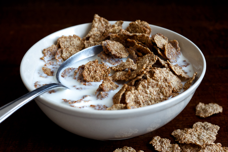spilt: Half eaten wheat bran breakfast cereal with milk in ceramic bowl. Moody lighting on dark rustic wood surface. Spilt flakes next to bowl. Spoon in bowl.