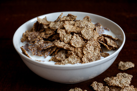 spilt: Wheat bran breakfast cereal with milk in ceramic bowl. Moody lighting on dark rustic wood surface. Spilt flakes next to bowl. Stock Photo
