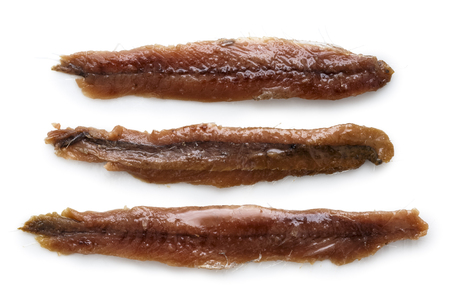 Three anchovy fillets with oil arranged symmetrically and isolated on white from above.